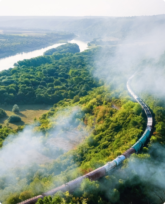 moving train on railway with high column of smoke flowing river hills and railway on the foreground